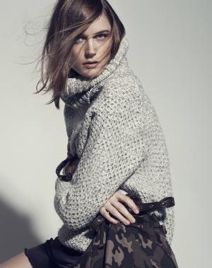 Femme Shapely Dressed In Col Roulé En Tricot Et Pantalon Blancs Gris Banque
